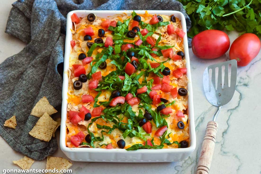 Taco casserole topped with olives, lettuce, and tomatoes