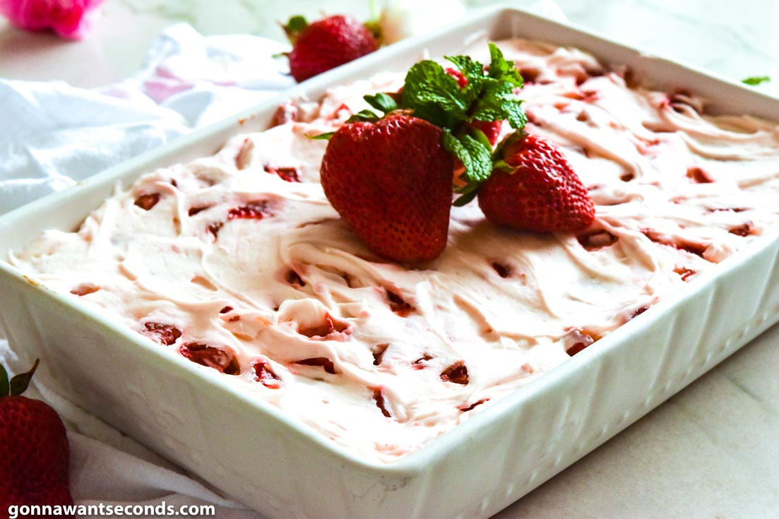 Strawberry jello cake with frosting, topped with fresh strawberries and mint sprigs, in a baking dish