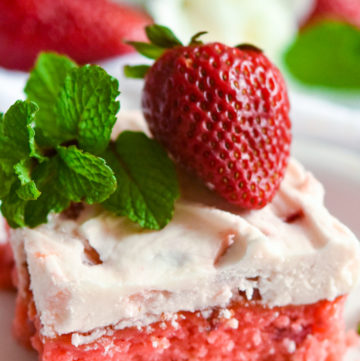 A slice of strawberry jello cake with frosting, topped with fresh strawberry and mint sprigs