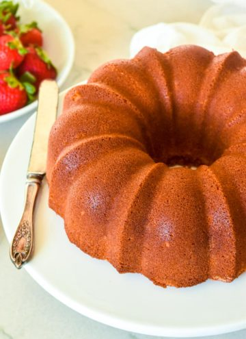 Old Fashioned Pound Cake on a plate with fresh strawberries on the side