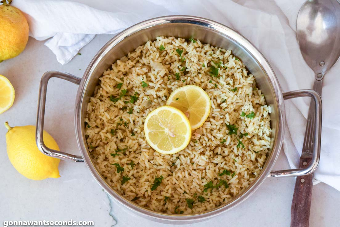 Greek Rice topped with sliced lemons, in a pot, top shot