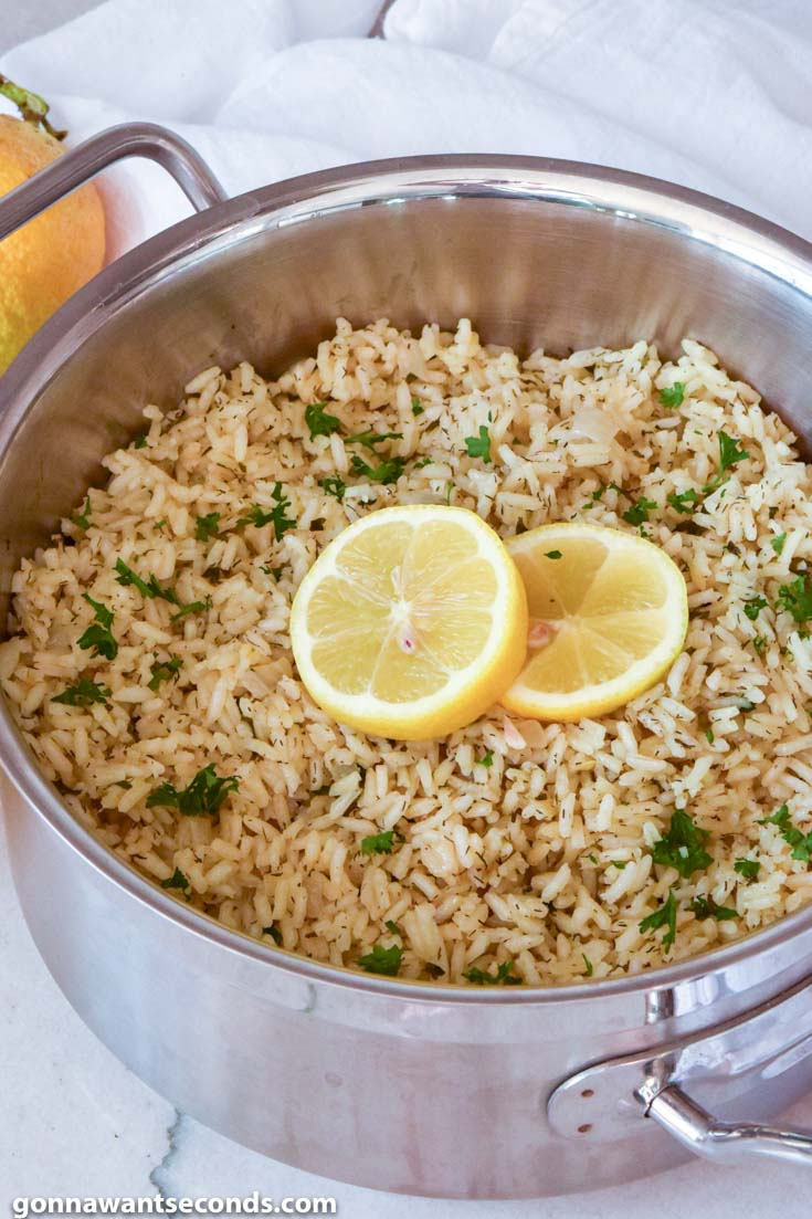 Greek Rice topped with sliced lemons, in a pot
