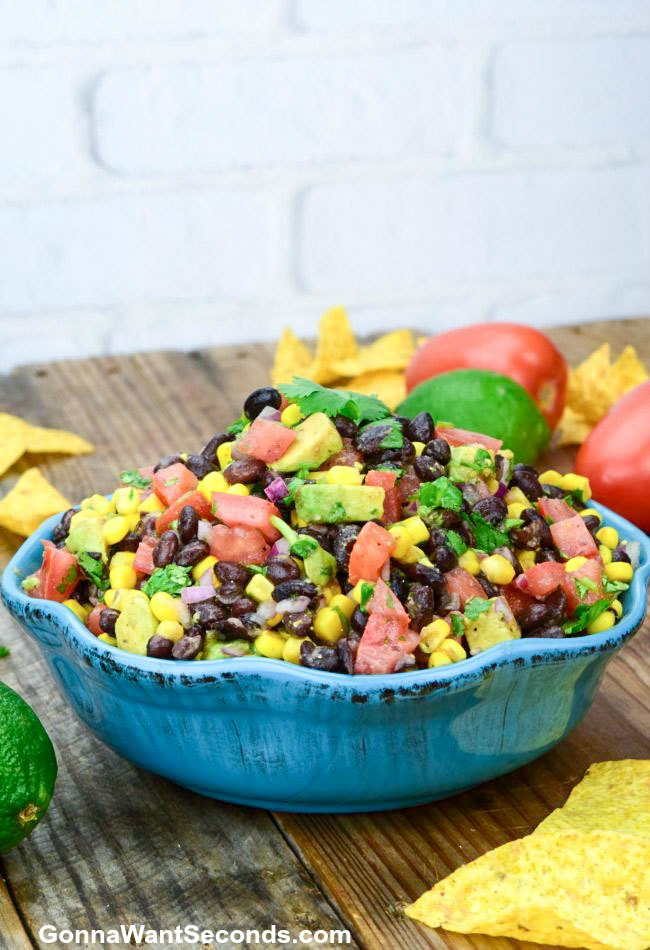 Cowboy Caviar in a blue bowl with tortilla chips and lime on the table