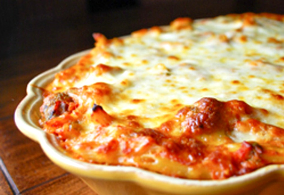 Baked Ziti topped with melted cheese, in a casserole dish