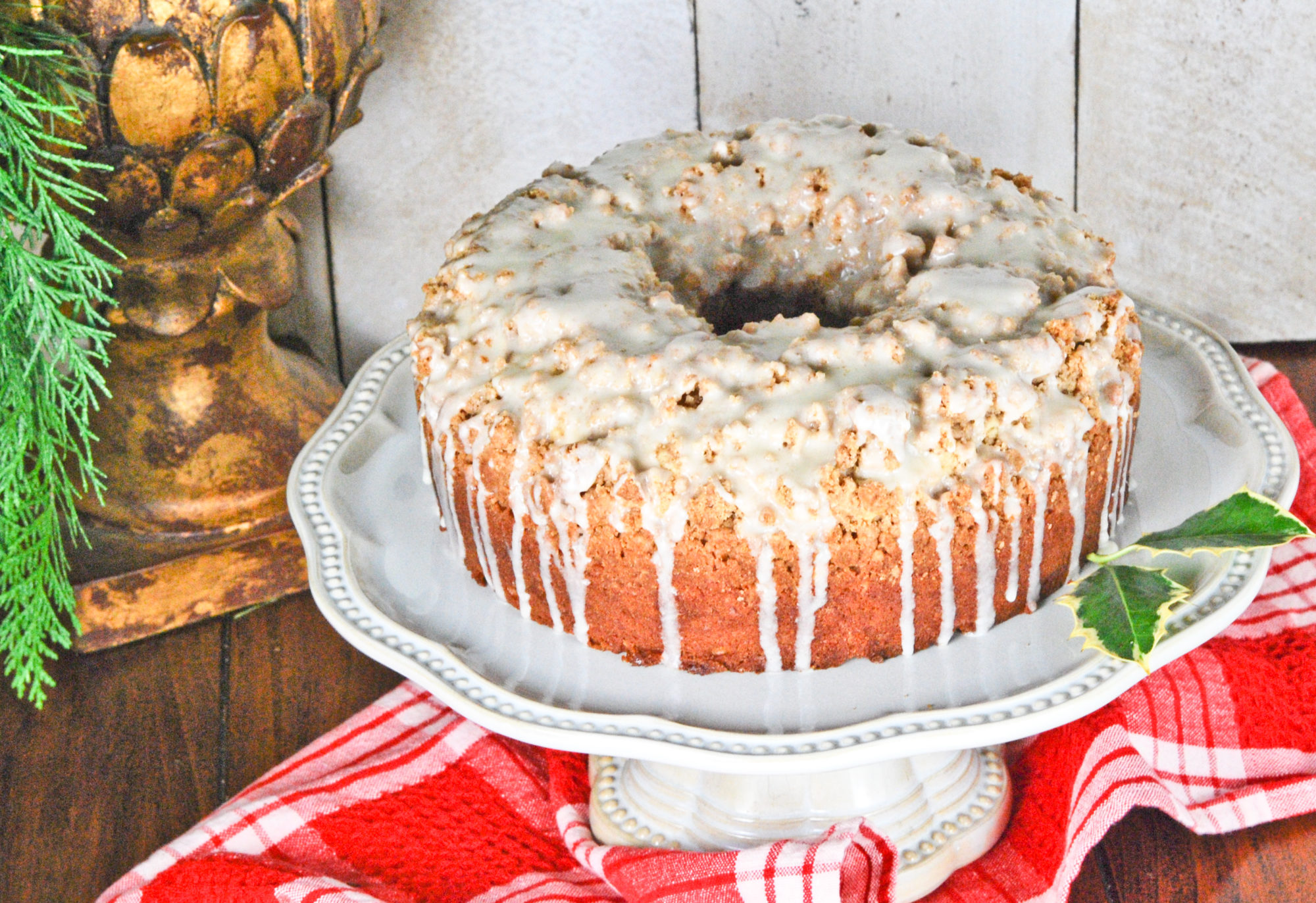 Eggnog Crumb Coffee Cake with nutmeg icing on a white cake stand