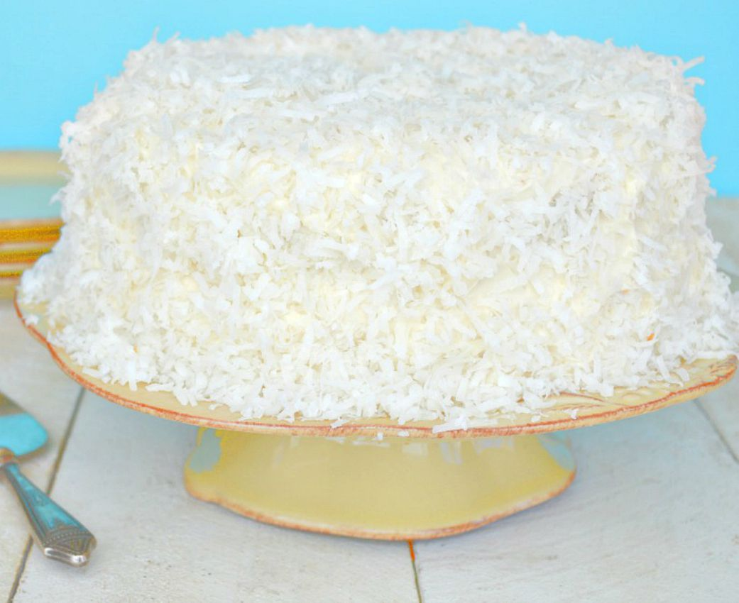 Coconut Cake with Coconut Cream Cheese Frosting on a cake stand