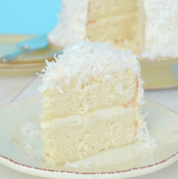 A slice of Coconut Cake with Coconut Cream Cheese Frosting on a plate