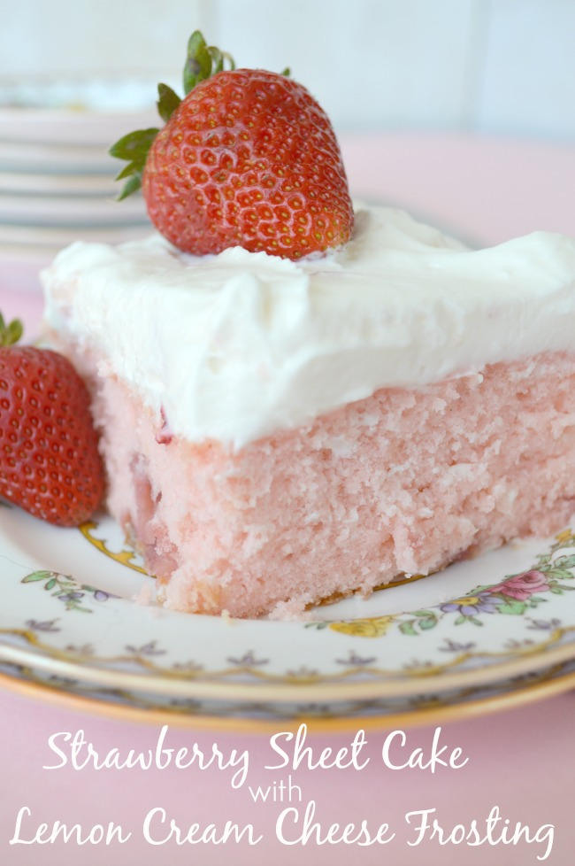 A slice of Strawberry Sheet Cake with Lemon Cream Cheese Frosting topped with fresh strawberry on a plate.