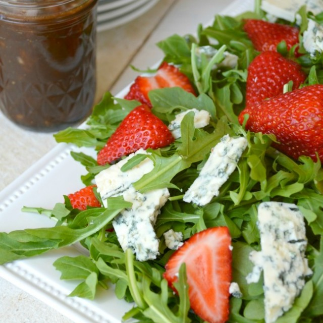 Strawberry Salad on a square serving plate, with a jar of sherry vinaigrette on the side