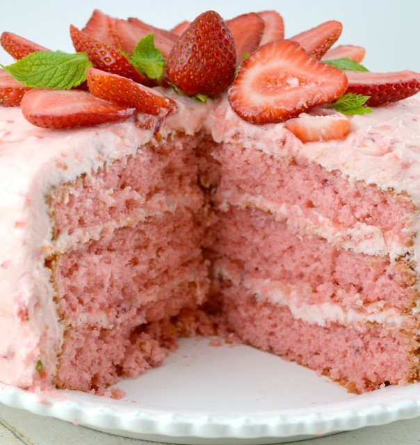 Triple Layer Strawberry Cake topped with fresh strawberries