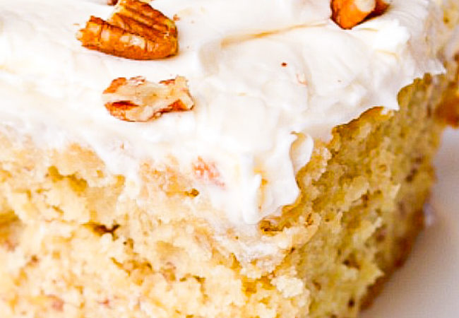 A slice of Banana Cake with Cream Cheese Frosting topped with pecans