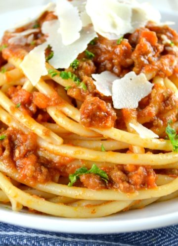 Authentic Ragu Bolognese Sauce topped with parmesan cheese on a plate