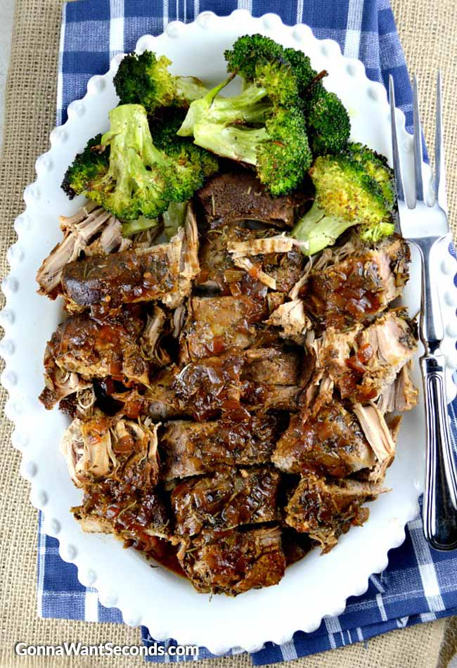Crock Pot Pork Tenderloin, garnished with broccoli florets in a white serving dish, with serving fork on the side