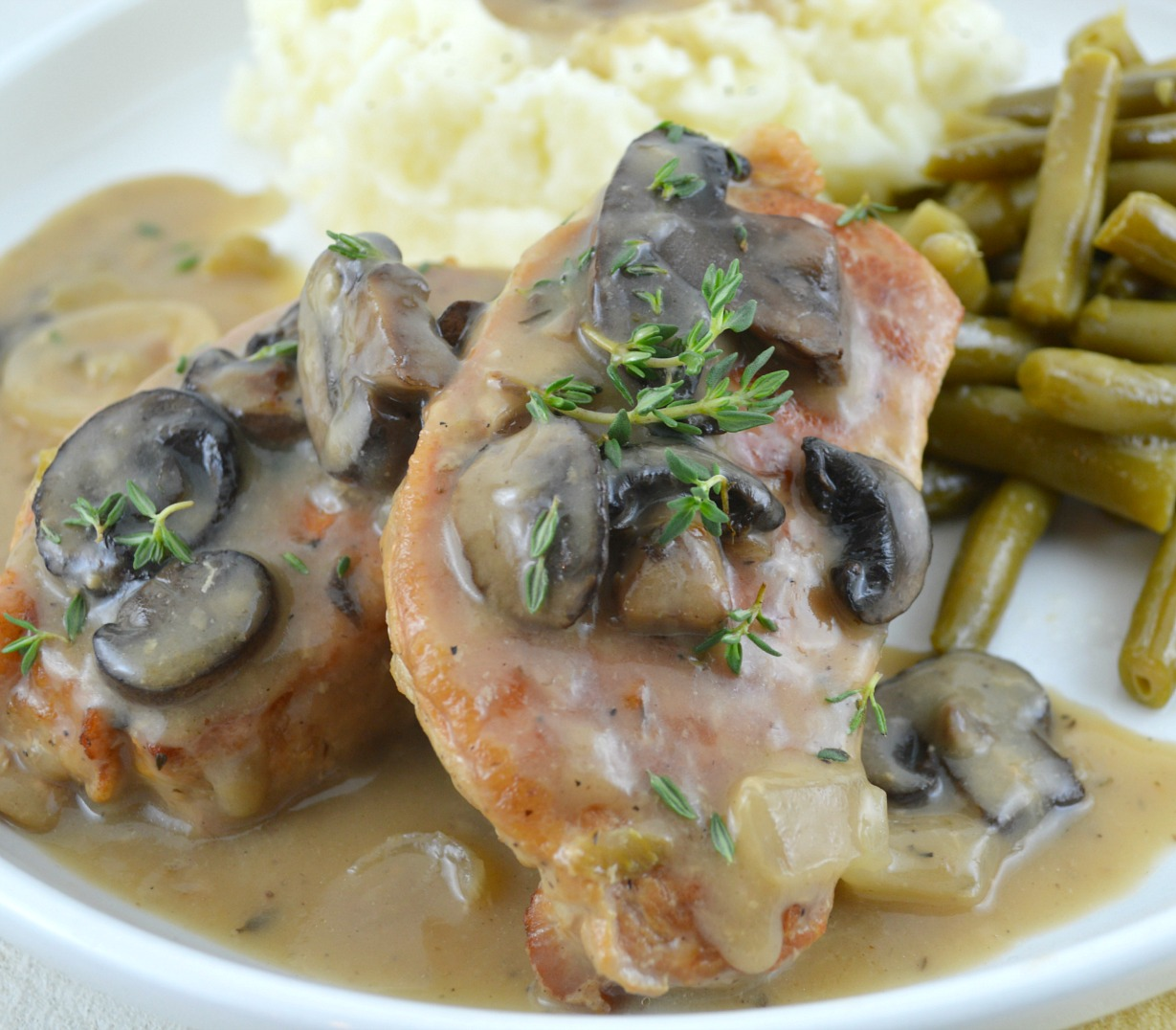 Crock Pot Pork Chops smothered with gravy, topped with mushroom, with green beans on the side