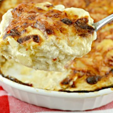 Scooping Potatoes Au Gratin from a casserole dish
