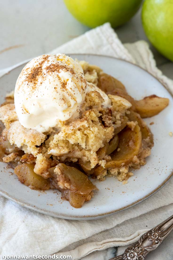 apple cobbler topped with vanilla ice cream, on a plate