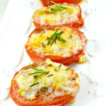 Baked Tomatoes topped with parmesan cheese, garnished with rosemary, arranged in a rectangular serving plate