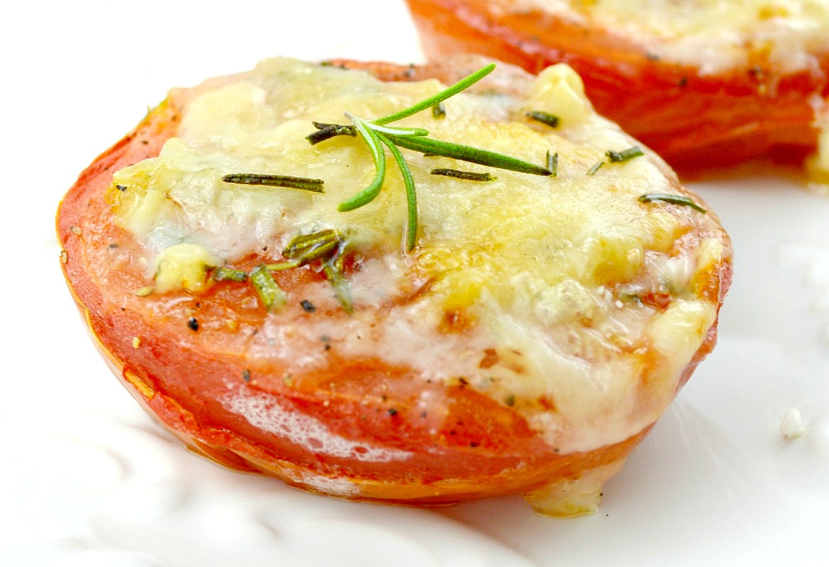 Baked Tomatoes topped with parmesan cheese, garnished with rosemary