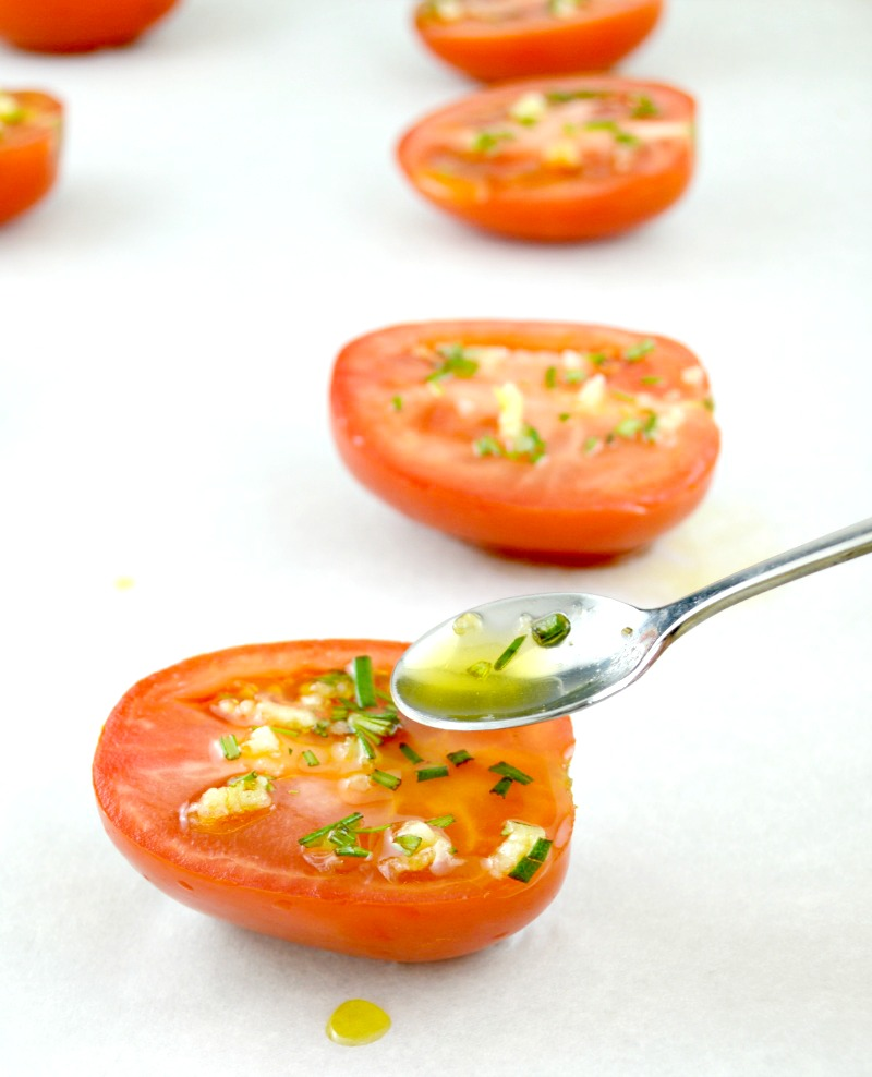 Adding oil on top of tomatoes using spoon