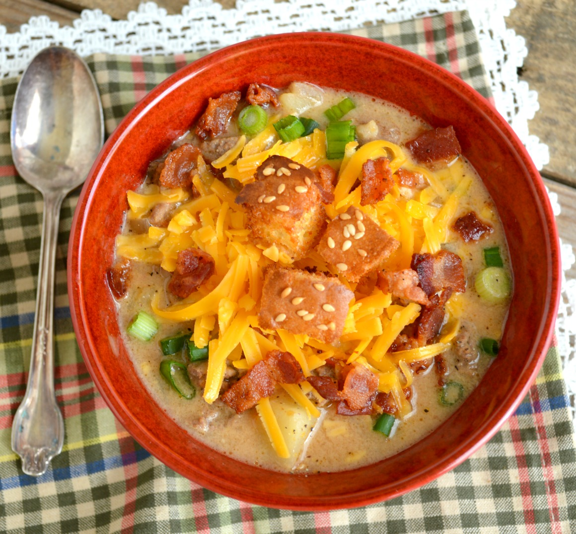 Cheeseburger Soup in a red bowl, topped with croutons and shredded cheese