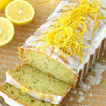 Glazed Lemon Zucchini Bread garnished with lemon peel on a chrome wire baking rack