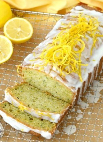 Whole lemon zucchini bread with lemon glaze on a cooling rack