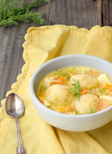 Matzo Ball Soup, garnished with fresh dill in a white soup bowl