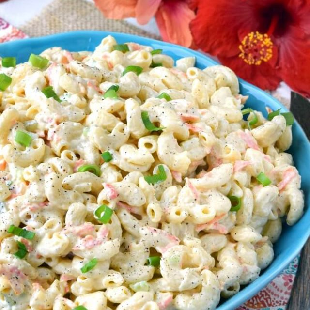 Authentic Hawaiian Macaroni Salad in a blue bowl with wooden serving fork and gumamela on the table