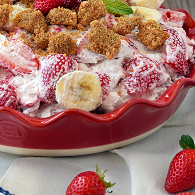 Strawberry Cheesecake Salad in a red shallow bowl, garnished with a fresh strawberry