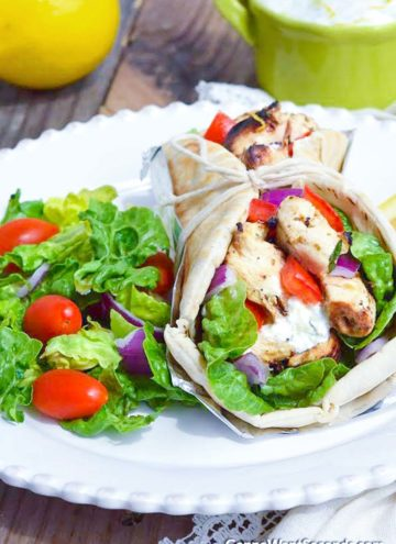 Wrapped Chicken Gyro with salad on the side, on a plate