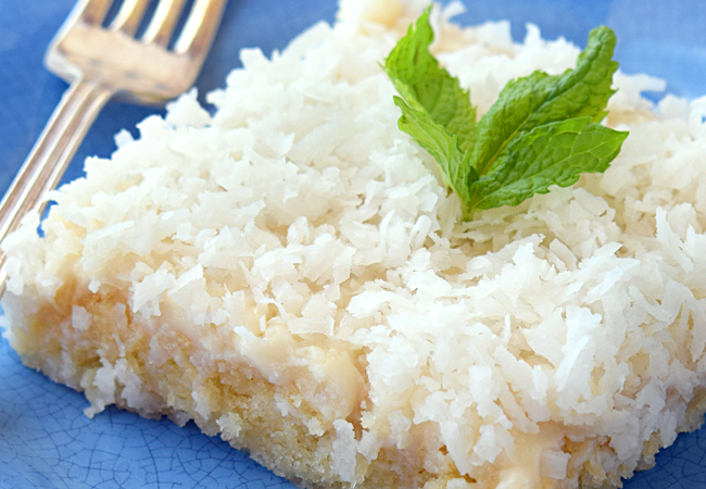 Coconut Sheet Cake garnished with mint leaves on a blue plate with fork.