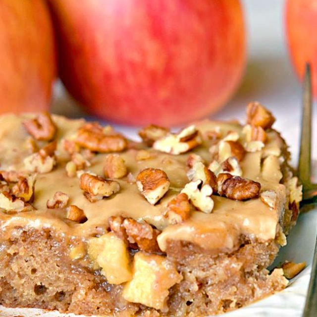 A slice of Caramel Apple Sheet Cake topped with caramel icing and chopped nuts