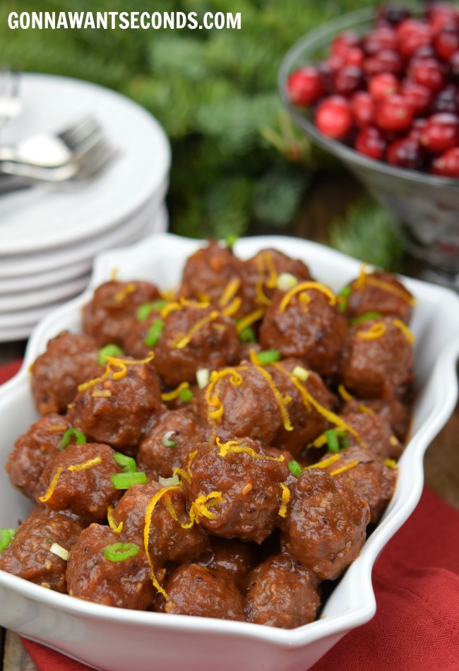 Cranberry Meatballs in a rectangle white serving dish, with saucers and fork on the side