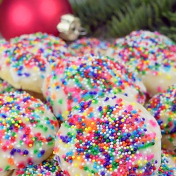 Italian Christmas Cookies piled on top of each other, with Christmas decorations at the back