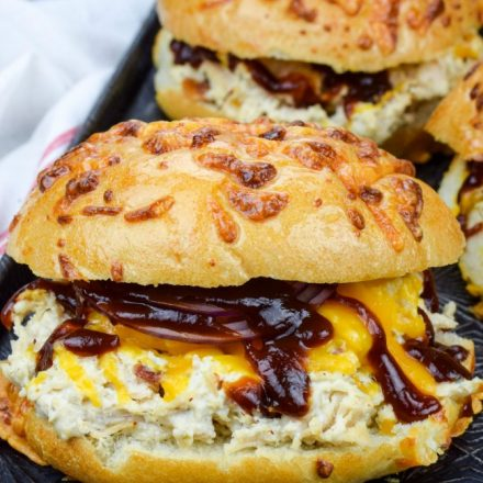 Crack Chicken with melted cheese, sliced red onions, and bbq sauce, in a roll