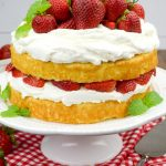 Strawberry Shortcake Cake topped with fresh strawberries and garnished with mint leaves, on a cake stand