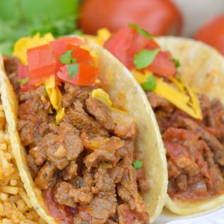 Carne Picada topped with cheese and tomatoes, in taco shells