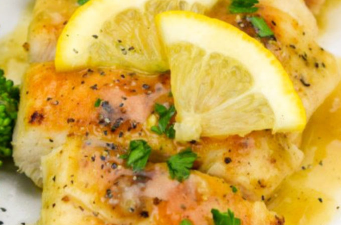 Lemon Pepper Chicken garnished with parsley and lemon wedges on a plate