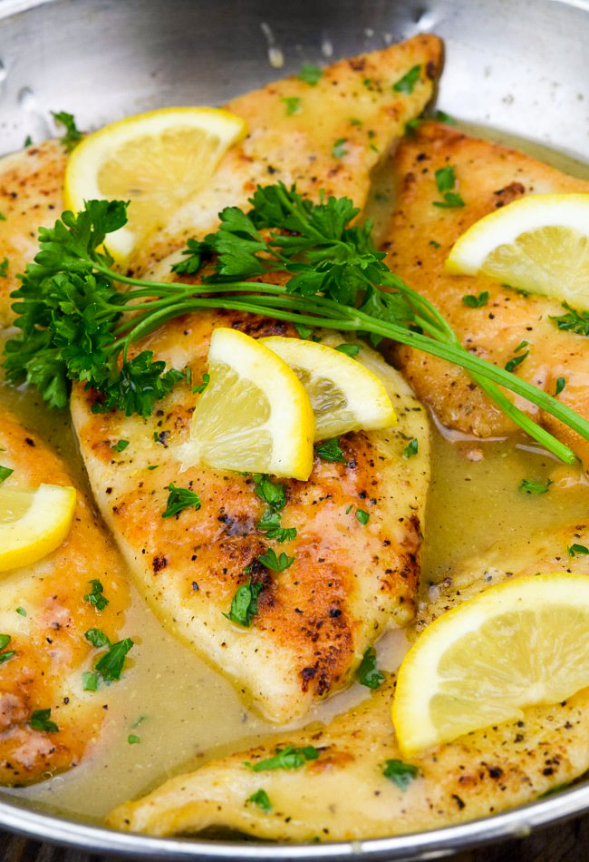 Lemon Pepper Chicken in a skillet garnished with lemon slices and parsley