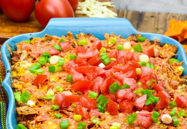 Easy Dorito Casserole topped with fresh tomatoes in a blue casserole dish