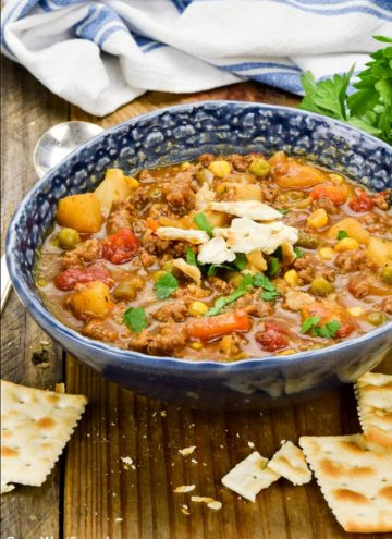 Hamburger Soup in a blue bowl, with crackers around