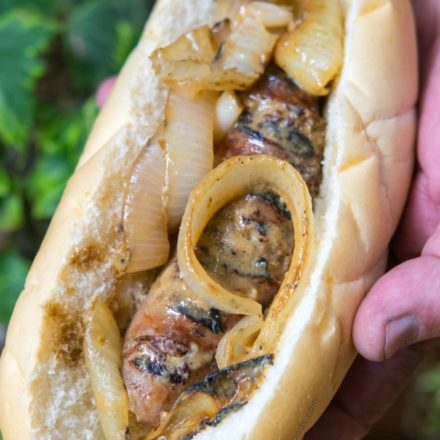 Beer Brats topped with caramelized onions held by hand