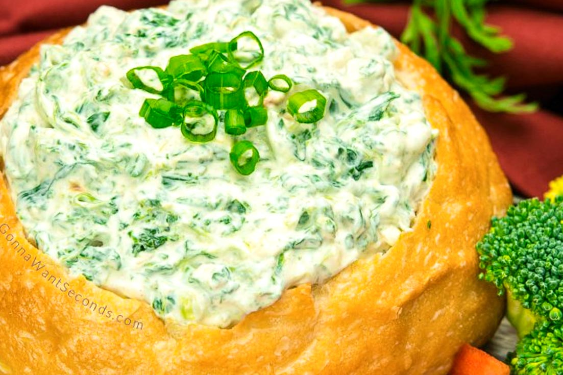 Knorr Spinach Dip in a round loaf of bread with sliced vegetables around