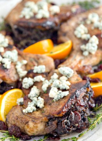 Stuffed Pork Chop topped with Bleu cheese on a white platter garnished with fresh orange.