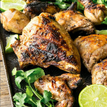 Grilled Pollo Asado on black sheet pan garnished with cilantro and lime
