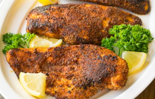 Blackened Chicken on a platter, garnished with lemon slices and parsley