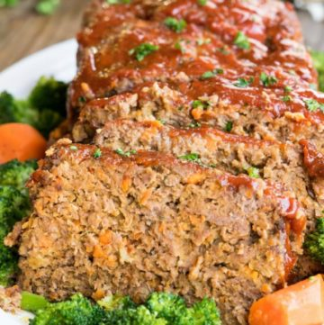 Sliced Alton Brown Meatloaf on a white platter surrounded by broccoli and carrots