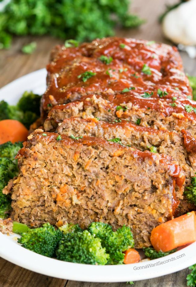 Alton Brown Meatloaf on a white platter surrounded by broccoli and carrots