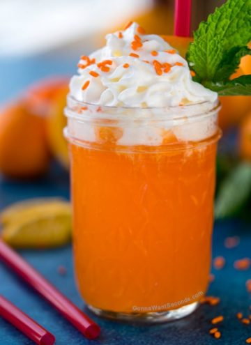 Creamsicle Drink in a mason jar topped with whipped cream, orange sprinkles, garnished with mint leaves