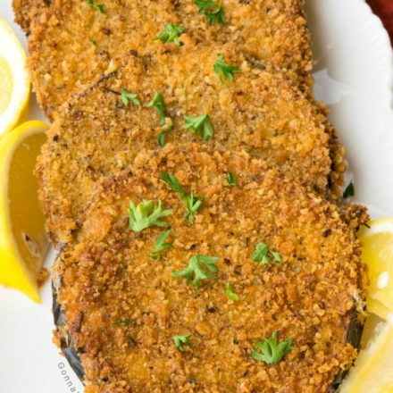 Fried Eggplant coated with panko breadcrumbs with lemon garnish on white rectangular serving dish